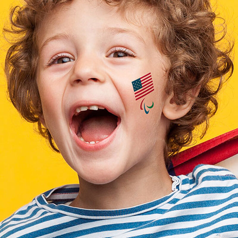 young boy wearing team usa paralympics tattoo on face image number null