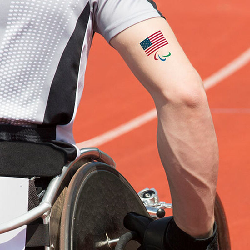 man in wheelchair wearing team usa paralympics tattoo on arm image number null